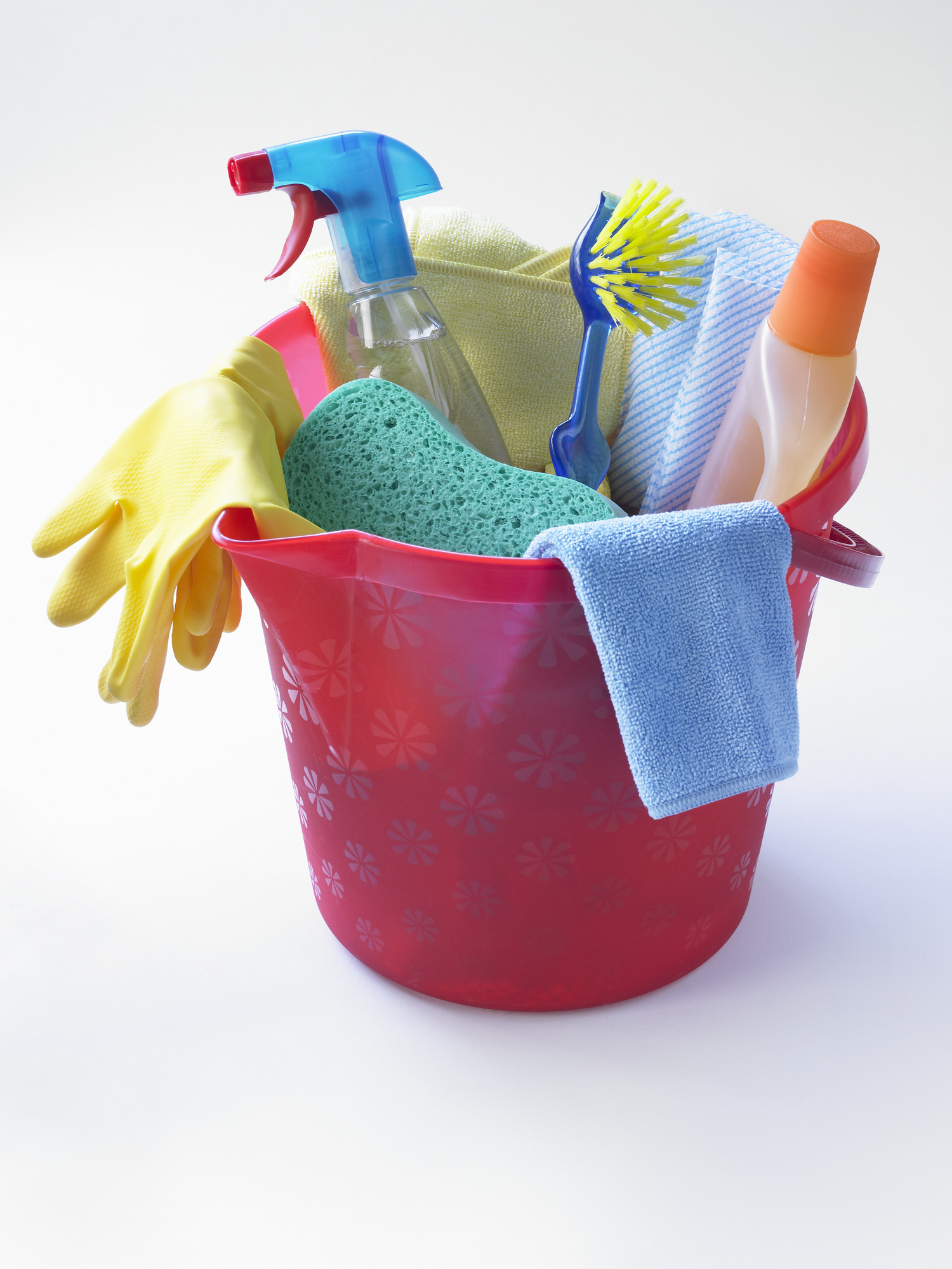 Pink plastic bucket containing cleaning products, including cloths, sponge, and disinfectant bottles