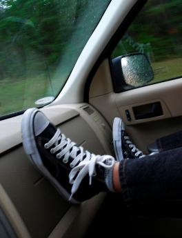 Boy's feet on dash of moving car.