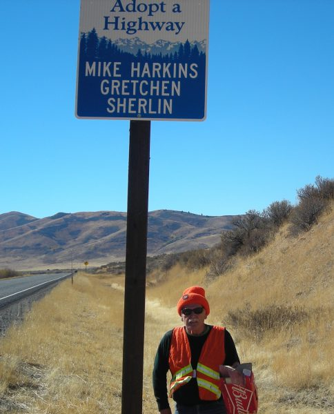Mike Harkins stands beneath the Adopt-A-Highway sign with his and Gretchen's name