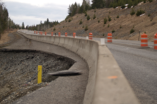 Barrels and guardrail separate traffic on US-95 from the Rock Creek slide.