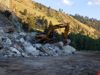 An excavator clears rock from the slide at MP 188 on US-95 near Riggins