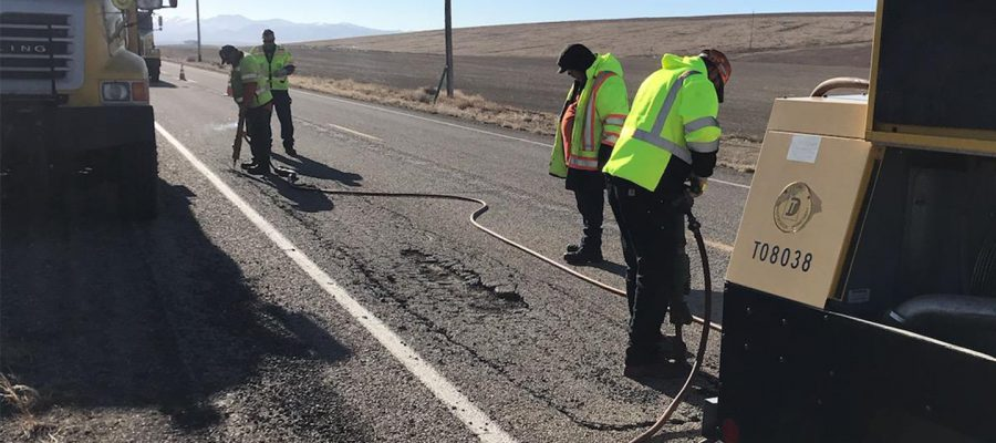 Four men on highway with jackhammers
